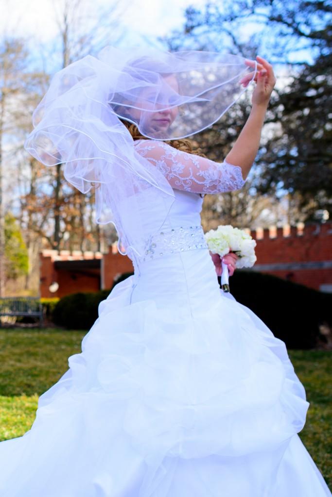 Bride hiding behind veil